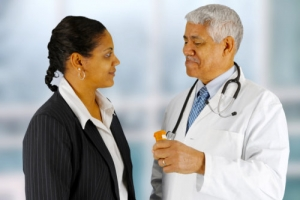 senior pharmacist with stethoscope talking with a female costumer